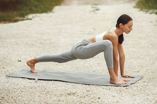 Pretty lady training on a summer beach. brunette doing yoga. girl in a sportsuit.