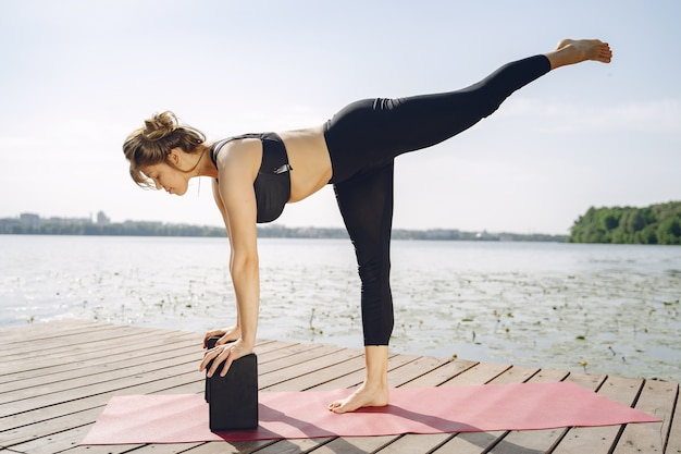 Pretty lady training in a summer park. brunette doing yoga. girl in a sportsuit.