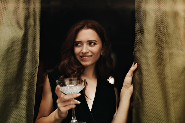 Pretty lady in velvet dress holds martini glass