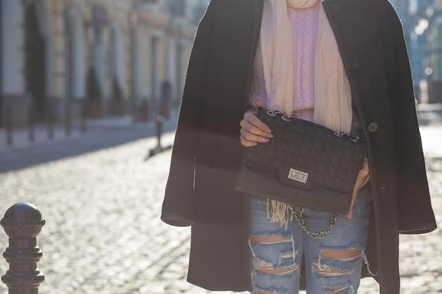 スタイリッシュなコート、熟したジーンズ、黒い革の財布を持ったセーターを着ているきれいな女性。テキスト用のスペース