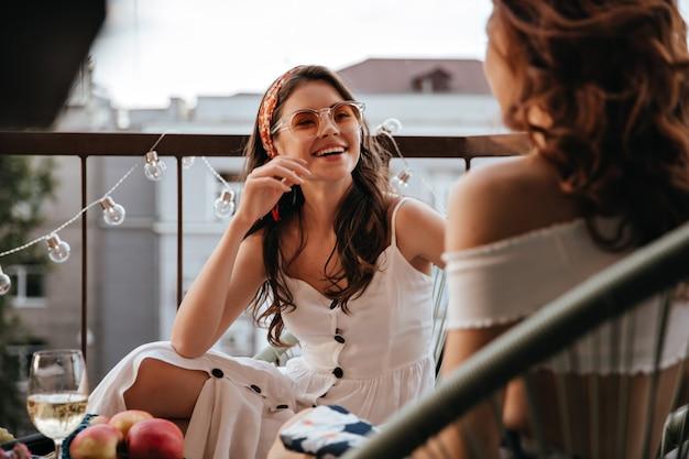 Bella signora in abito bianco parla con la sua amica
