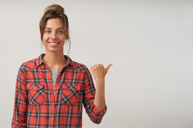 Симпатичная дама с очаровательной улыбкой, показывающая большой палец в сторону, в клетчатой рубашке, с естественным макияжем, весело выглядит, стоит