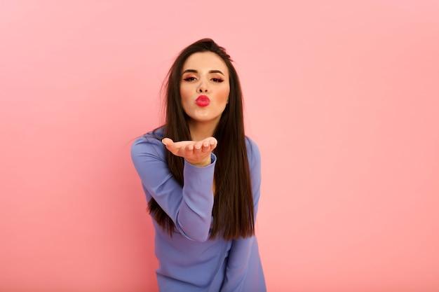 빨간 큰 입술과 갈색 머리 긴 헤어 스타일 스튜디오에서 분홍색 배경에 포즈 예쁜 아가씨. 그녀의 매끈한 몸매에 세련된 드레스. 데 콜테와 긴 소매. 젊은 섹시 한 여자, 오픈 입