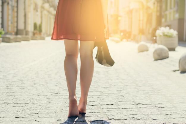 맨발로 거리를 걷는 하이힐을 신고 손에 신발을 가진 예쁜 아가씨. 후면보기 사진 뒤에 자른 후면을 닫습니다. 태양 광선 광선 샤인 햇살 버스트 샤이니 플레어 효과 섬광 스파클