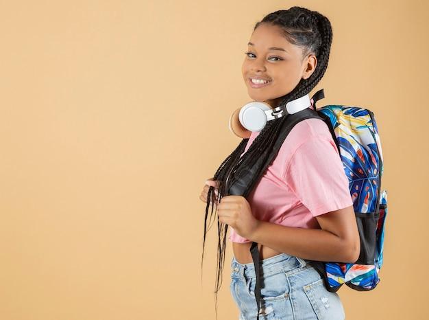 헤드폰과 배낭을 메고 고등학교에 다니는 예쁜 라틴 아메리카 소녀