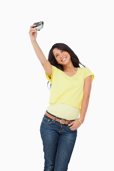 Pretty latin student taking a picture of herself against white background