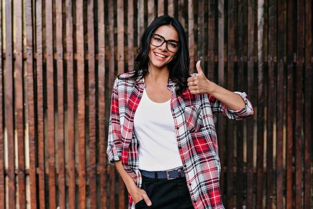 나무 벽에 엄지 손가락 최대 포즈 꽤 라틴 여자. 편안하고 매력적인 소녀의 야외 사진은 안경과 가죽 벨트를 착용합니다.