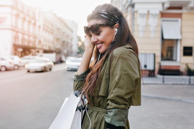 Donna abbastanza latina con nastro nero che ride per strada, ascoltando musica in auricolari