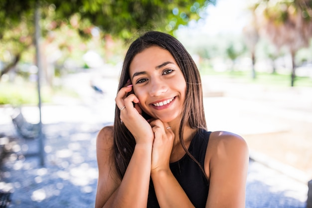 Pretty latin woman with charming smile looking at camera while standing on street