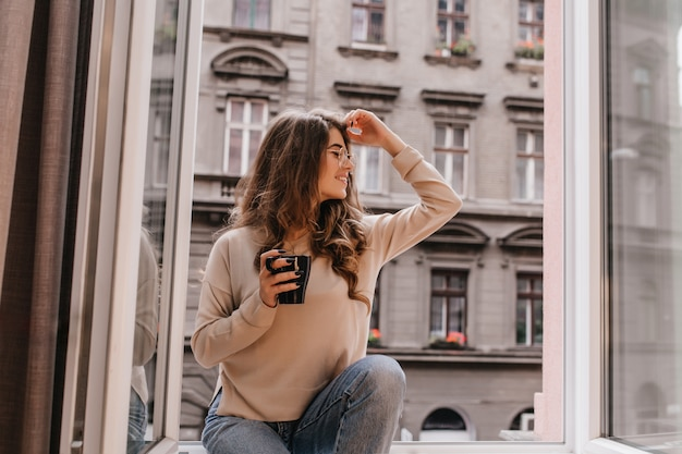 Pretty laughing female model in glasses sitting on sill with cup of coffee