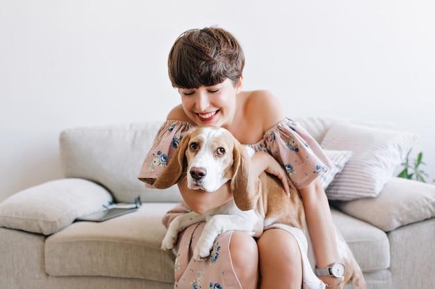 ソファでポーズをとっている間、美しい恥ずかしがり屋の子犬を保持しているかなり笑っている女性モデル