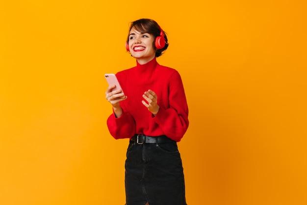 Довольно смеющаяся женщина, держащая смартфон на желтой стене