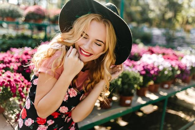 ぼやけた自然の中でポーズをとっているかわいいling-haired女性。オレンジリーに朝を過ごす風の強い白人女性モデル。