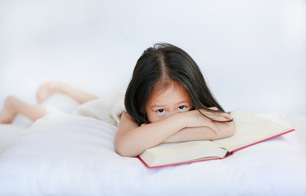 Pretty little asian child girl lying with hardcover book on pillow on white background.