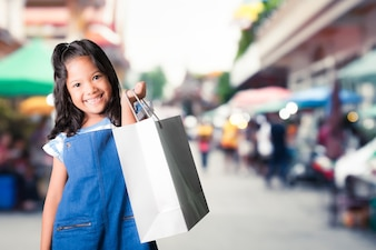 Pretty little asian girl holding shopping bags