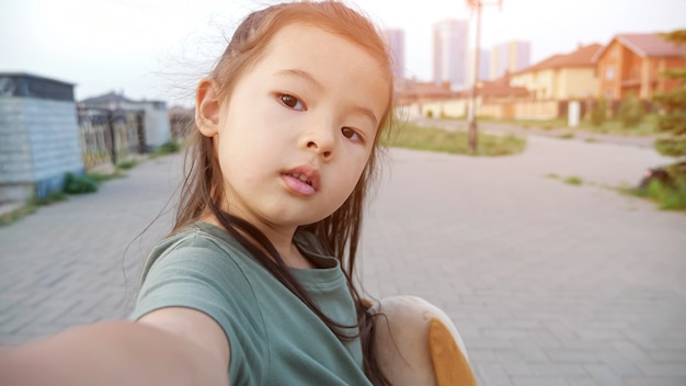 Pretty little asian girl with dog makes selfie on embankment