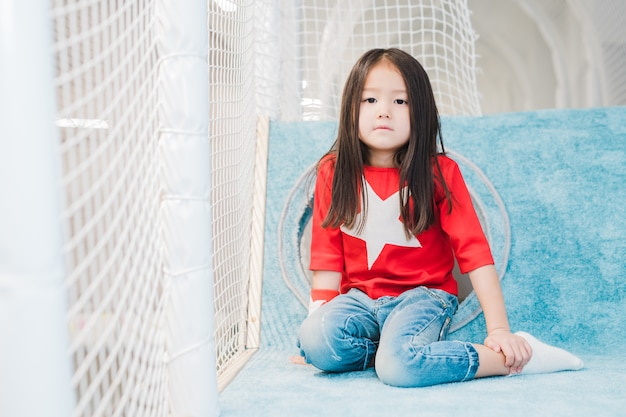 Pretty little asian girl with long hair wearing costume of super girl looking at you on play area