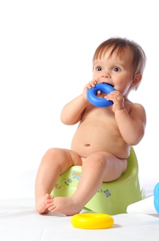 Pretty little baby sits on green potty and plays loved toy