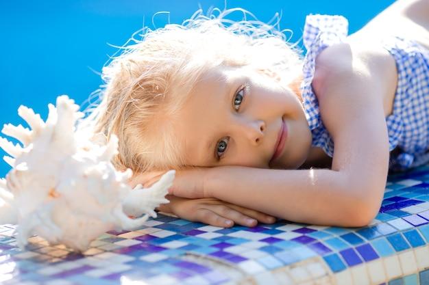 Симпатичная маленькая блондинка в соломенной шляпе и купальнике лежит на берегу бассейна с ракушкой