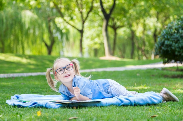A pretty little blonde girl with blonde hair and reading glasses reading a book on a park