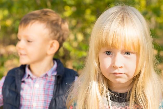 예쁜 파란 눈의 금발 소녀가 카메라를 열심히 쳐다보고 어린 소년이 뒤에서 옆을 바라보고 있다