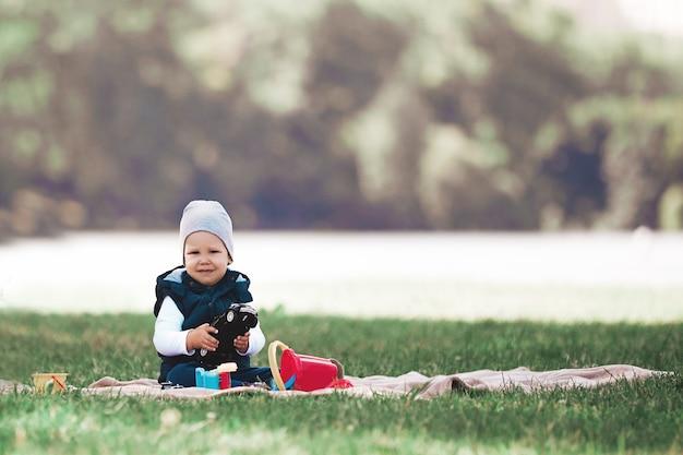 공원에서 잔디밭에 앉아 장난감을 가지고 노는 예쁜 소년