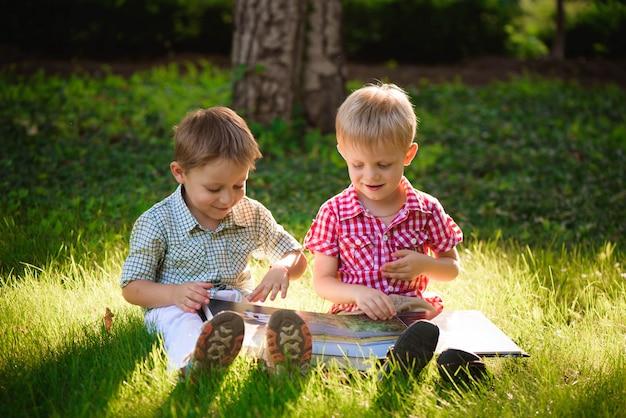A pretty little boys reading a book on a green grass.