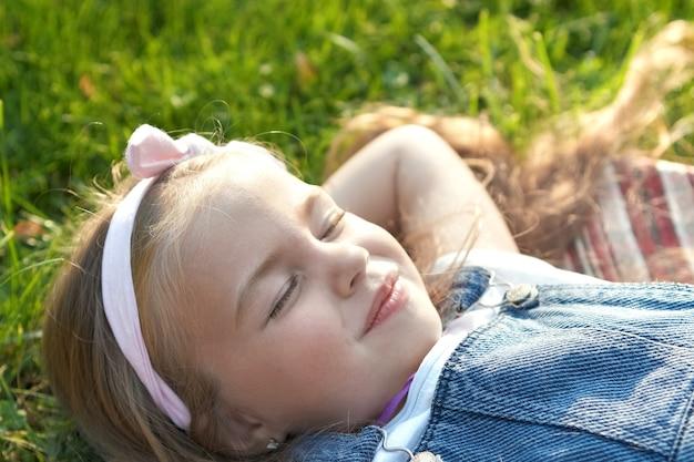 昼寝をしている夏に緑の草の上に横たわっているかわいい子供の女の子。