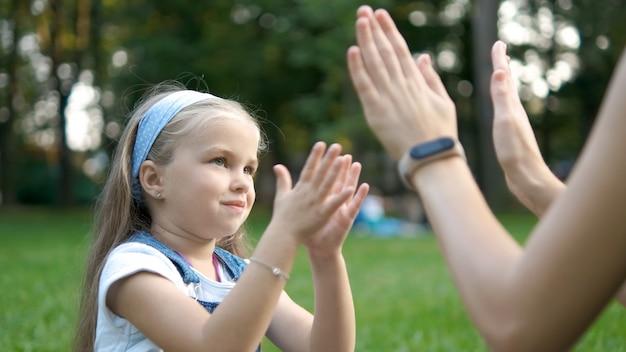 Довольно маленькая девочка ребенка играет в игру со своей мамой, хлопая в ладоши вместе на открытом воздухе в зеленом летнем парке.