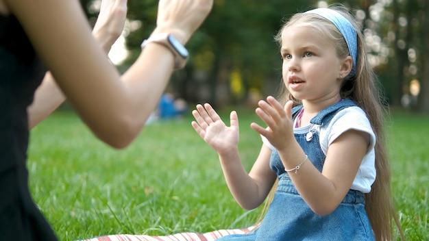 緑の夏の公園で屋外で両手で母親とゲームをしているかわいい子供の女の子。