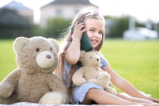 夏の屋外で幸せそうに笑っている携帯電話で話している彼女のテディベアのおもちゃと一緒に夏の公園に座っているかわいい子供の女の子。
