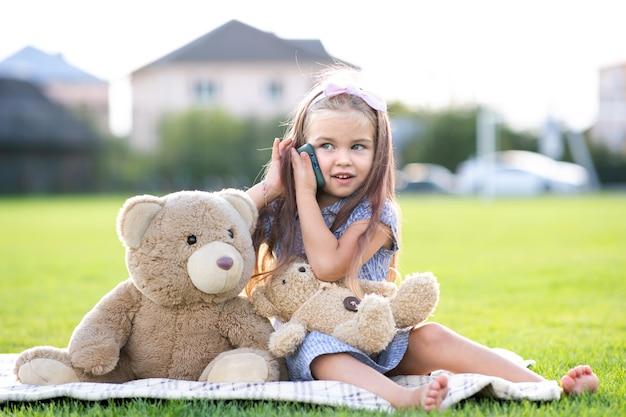 夏の屋外で幸せそうに笑っている携帯電話で話している彼女のテディベアのおもちゃで夏の公園に座っているかわいい子供の女の子。