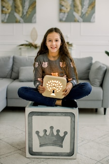 Pretty little child girl, sitting on the modern cube stool, holding beautiful wooden hand made night lamp with cut out tree picture.
