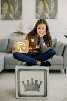 Симпатичная маленькая девочка, сидящая на табурете современного куба, держа в руках красивый деревянный ночник ручной работы с вырезанным изображением дерева.