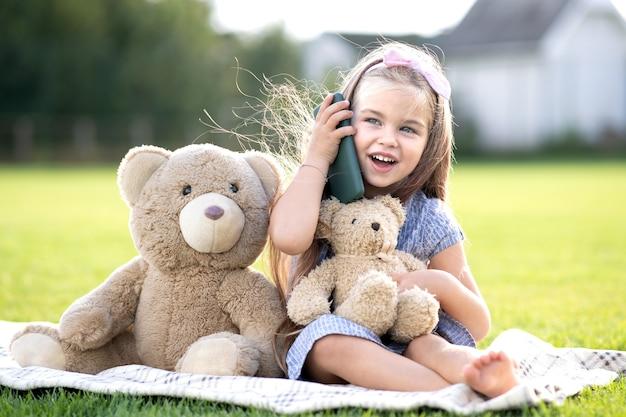 夏の屋外で幸せそうに笑って携帯電話で話しているかわいい子の女の子。