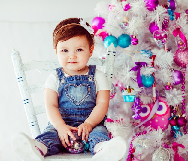 Pretty little child sits on chair before christmas tree