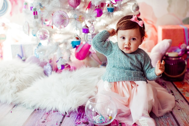 Pretty little child sits on fluffy carpet before christmas tree