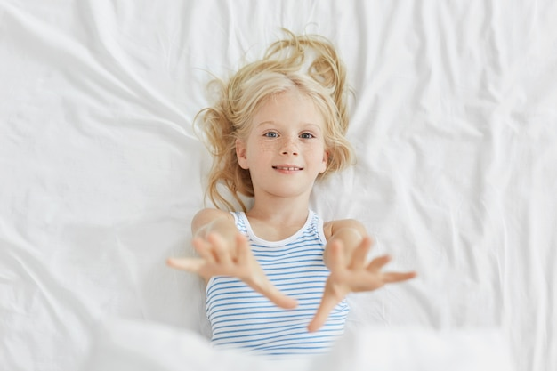 Pretty little child stretching her hands while lying in bed. blue eyed small girl having rest in bed