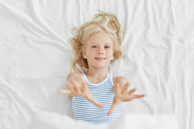 침대에 누워있는 동안 그녀의 손을 스트레칭 예쁜 아이. 침대에서 휴식을 갖는 푸른 눈의 작은 소녀
