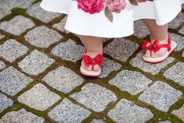 Pretty  little girl for 1 year old taking first step. cute legs of a small child in red sandals on the street close-up