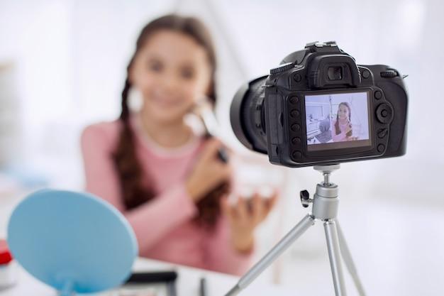カメラの前でメイクアップアーティストのように振る舞うかわいい女の子