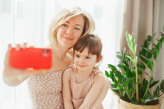 Милая маленькая девочка и ее молодая мама сидят вместе и обнимаются, делая селфи на красном телефоне