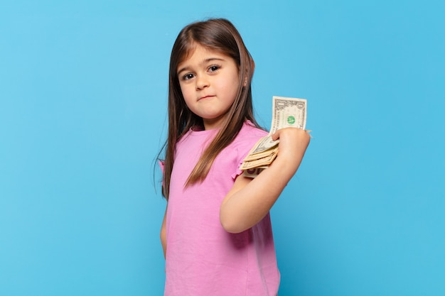 Pretty little girl angry expression and dollar banknotes