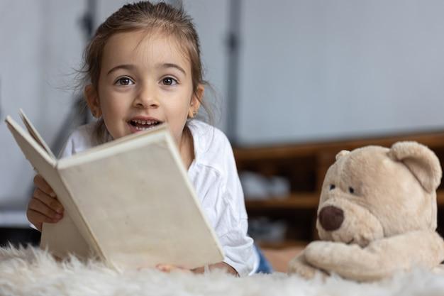 Милая маленькая девочка дома, лежа на полу со своей любимой игрушкой и читает книгу.