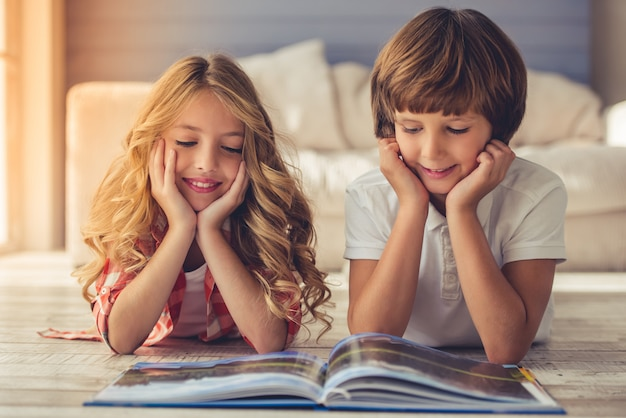 Pretty little girl and boy are reading book and smiling.