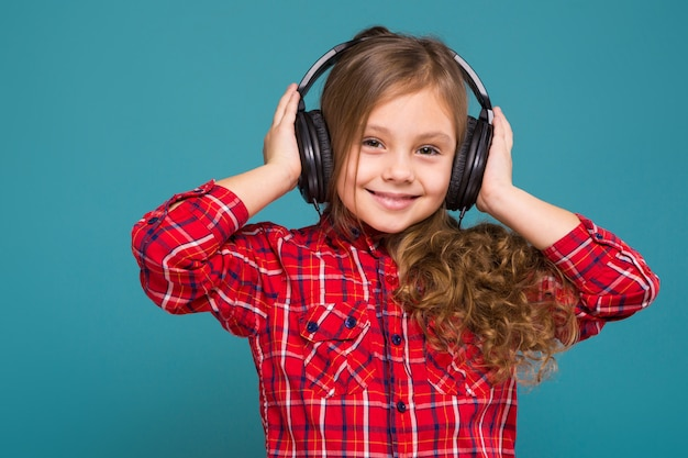 Pretty, little girl in checkered shirt and earphones with brown hair