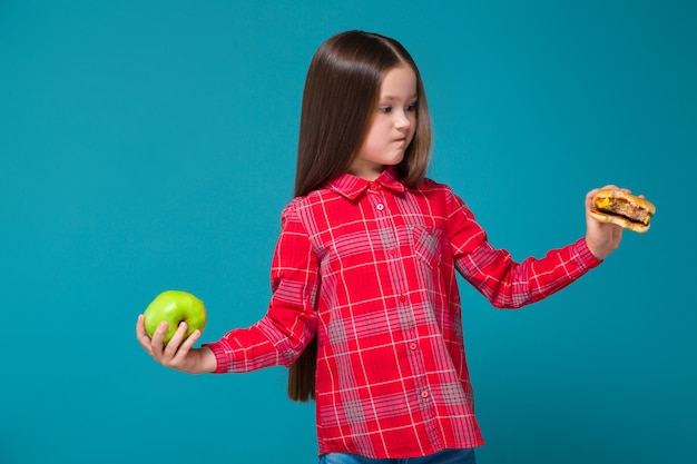 Pretty, little girl in checkered shirt with brunet hair hold burger