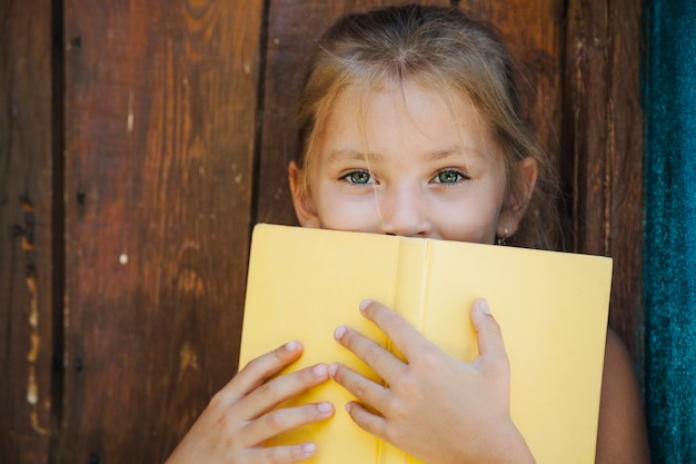 Pretty little girl covering with book