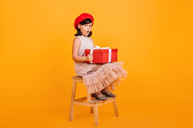 Bambina graziosa in vestito che si siede sulla sedia e che tiene grande scatola attuale. ragazzo francese con regalo di compleanno.