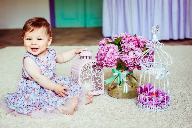 Pretty little girl in dress with flowers sits before pink lantern and bouquet of lilacs